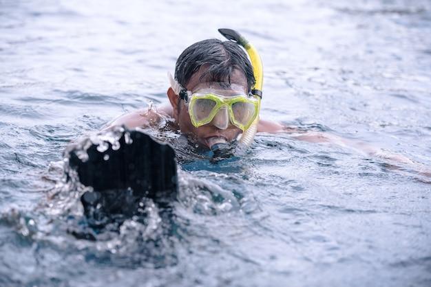 Junger mann, der unter wasser in den tragenden schnorchel- und unterwasseratemgerätschuhen des pools schwimmt (antriebspantoffel, tauchschuhe).