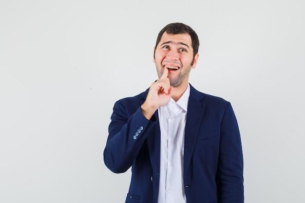 Junger mann, der unter zahnschmerzen im hemd, in der jacke leidet und unangenehm aussieht
