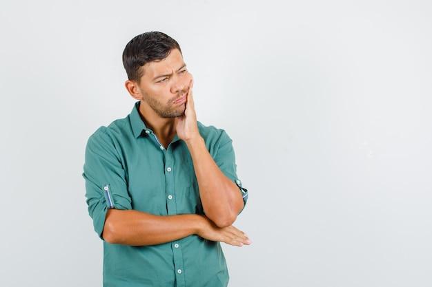 Junger mann, der unter zahnschmerzen im hemd leidet und traurig schaut