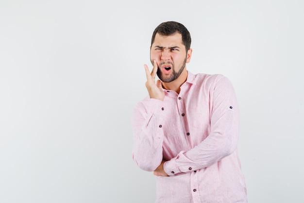 Junger mann, der unter zahnschmerzen im rosa hemd leidet und ängstlich schaut
