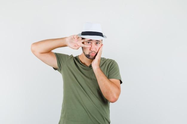 Junger mann, der v-zeichen auf auge in grünem t-shirt und hut zeigt und niedlich schaut