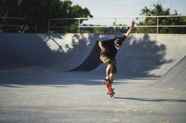 Junger mann, der verschiedene tricks mit einem skateboard im park tut, der eine medizinische gesichtsmaske trägt
