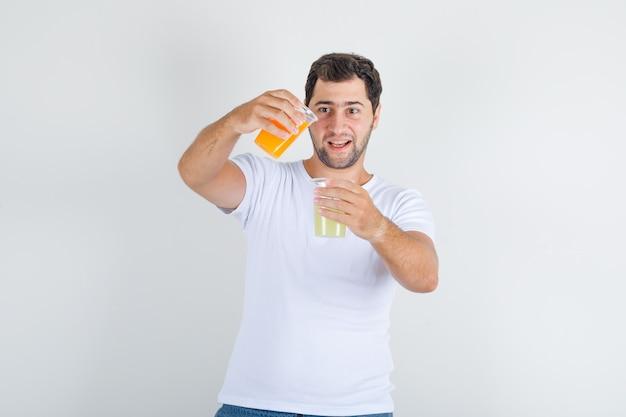 Junger mann, der verschiedenen saft mischt, indem er in weißes t-shirt gießt und verrückt aussieht