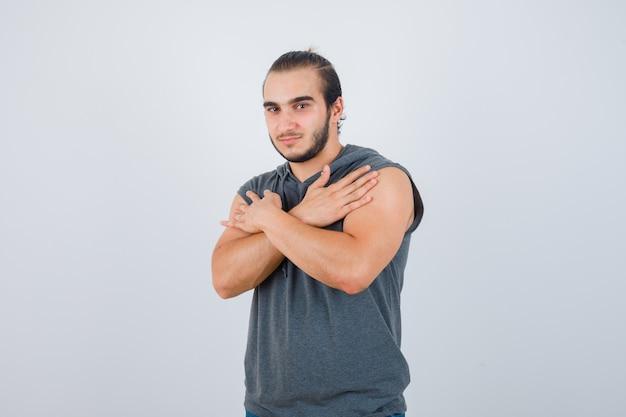 Junger mann, der verschränkte arme auf brust in ärmellosem kapuzenpulli hält und intelligent aussieht. vorderansicht.