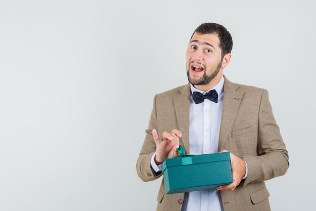 Junger mann, der versucht, geschenkbox im anzug zu öffnen und neugierig schaut. vorderansicht.
