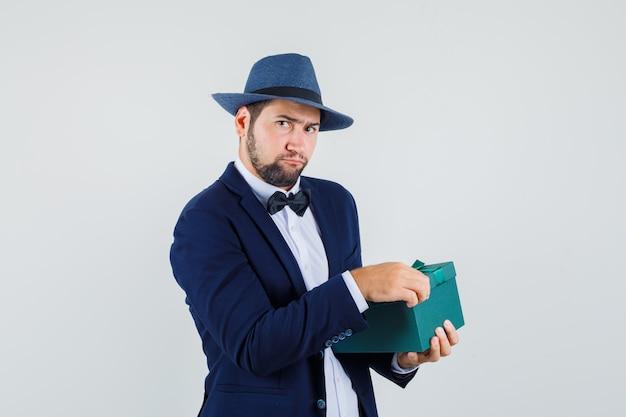 Junger mann, der versucht, geschenkbox in anzug, hut zu öffnen und zögernd aussieht. vorderansicht.
