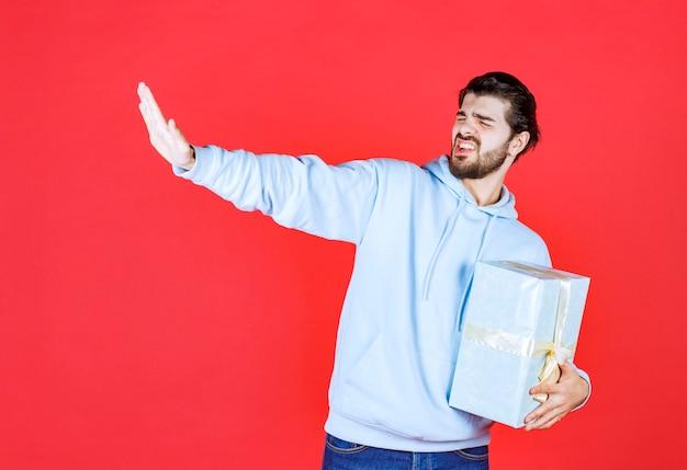Junger mann, der versucht, seine geschenkbox zu retten