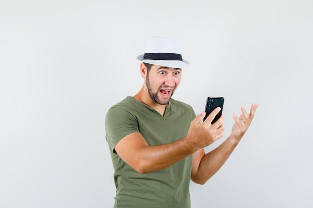 Junger mann, der video-chat im grünen t-shirt und im hut hat und erstaunt schaut