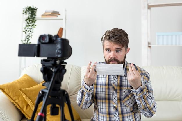 Junger mann, der video zu hause mit gesichtsmaske aufzeichnet
