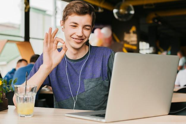 Junger mann, der videoanruf auf laptop tut