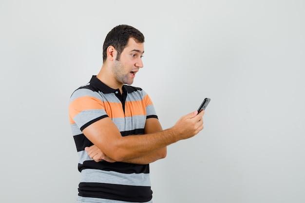 Junger mann, der videoanruf im t-shirt macht und konzentriert schaut