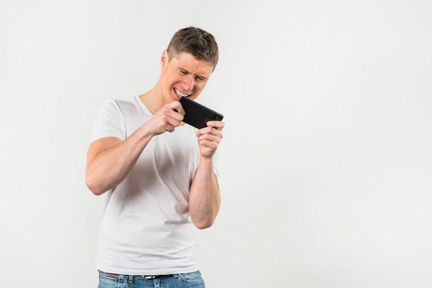 Junger mann, der videospiel am handy gegen weißen hintergrund spielt