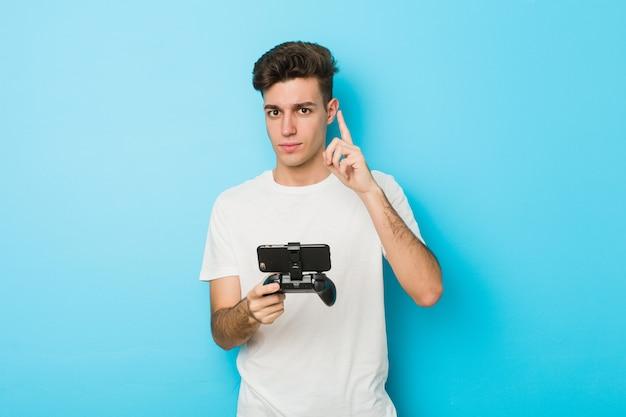Junger mann, der videospiele mit dem telefon zeigt nummer eins mit dem finger spielt
