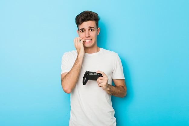 Junger mann, der videospiele mit spielendem fingernagel spielt, nervös und sehr ängstlich