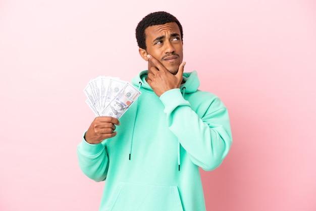 Junger mann, der viel geld über isoliertem rosa hintergrund mit zweifeln nimmt