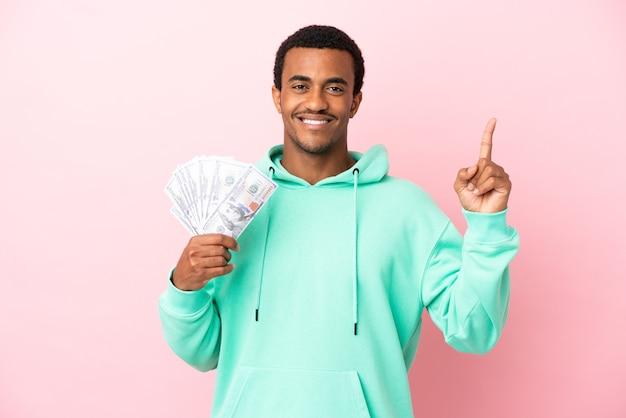 Junger mann, der viel geld über isoliertem rosa hintergrund nimmt und auf eine großartige idee hinweist