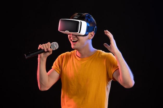 Junger mann, der virtuelle realität spielt und auf der dunklen oberfläche singt