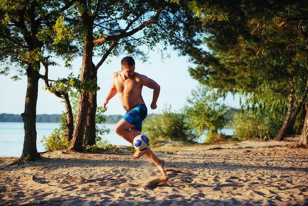 Junger mann, der volleyball am strand spielt