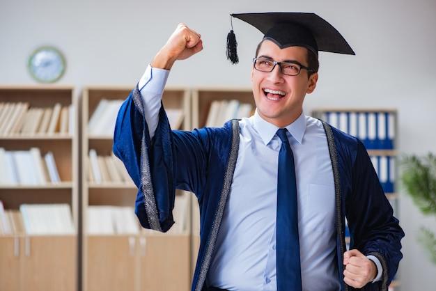 Junger mann, der von der universität graduiert