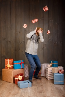Junger mann, der von fallenden weihnachtsgeschenken über hölzerner oberfläche versteckt