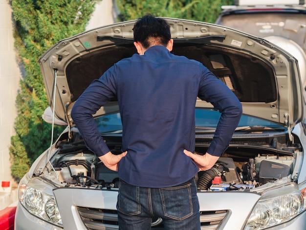 Junger mann, der vor defektem auto für die prüfung des autos steht