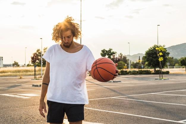 Junger mann, der vor gericht basketball spielt