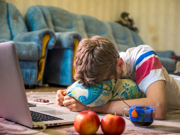 Junger mann, der vor laptop beim lügen auf dem bodenteppich schläft