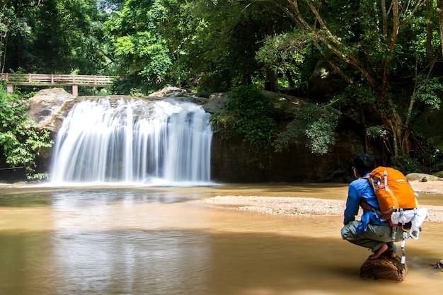Junger mann, der vor wasserfall mit dem betrachten des wasserfall- und reiserucksacks in thailand steht