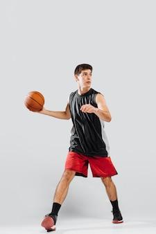 Junger mann der vorderansicht, der basketball spielt