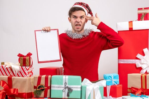 Junger mann der vorderansicht, der fingerpistole zu seiner schläfe setzt, die um weihnachtsgeschenke sitzt