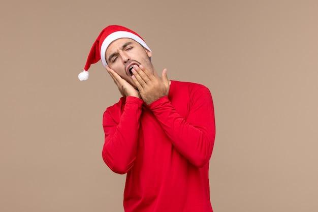 Junger mann der vorderansicht, der gähnt und versucht, auf weihnachtsfeiertag der braunen hintergrundemotion zu schlafen