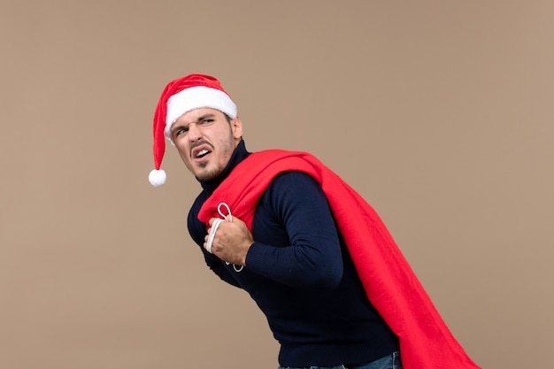 Junger mann der vorderansicht, der geschenkbeutel auf weihnachtsfeiertags-weihnachtsmann des braunen bodens trägt
