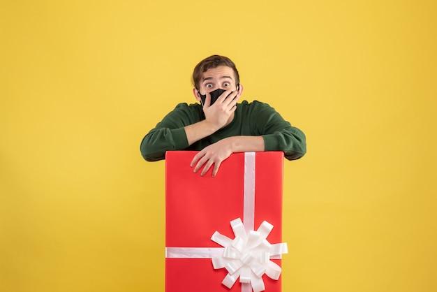 Junger mann der vorderansicht, der hand zu seinem mund hinter großer geschenkbox auf gelb setzt