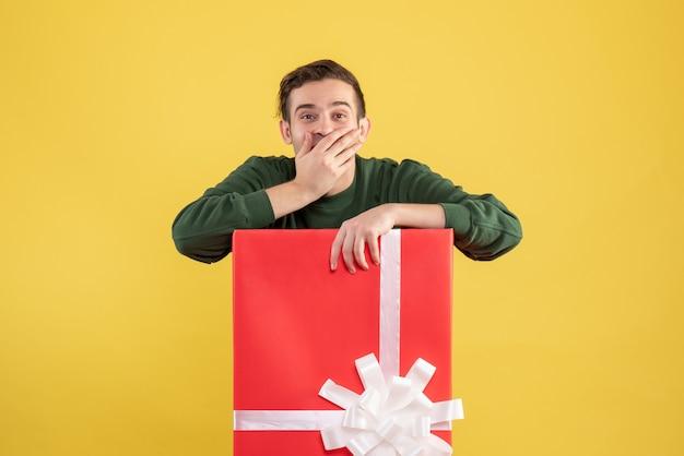 Junger mann der vorderansicht, der hand zu seinem mund stellt, der hinter großer geschenkbox auf gelb steht