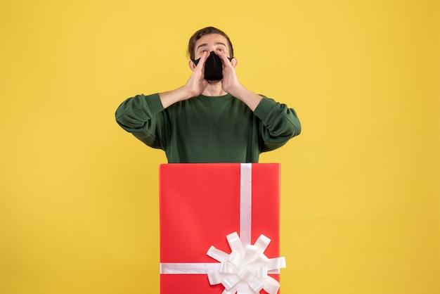 Junger mann der vorderansicht, der jemanden anruft, der hinter großer geschenkbox auf gelb steht