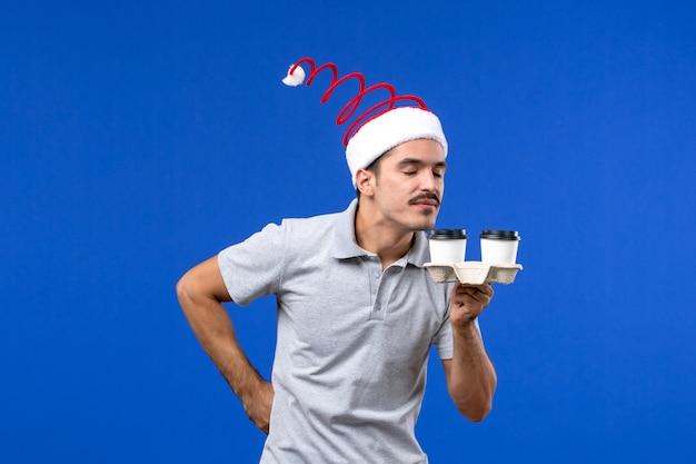 Junger mann der vorderansicht, der kaffeetassen auf männlichem gefühlskaffeemensch der blauen wand hält
