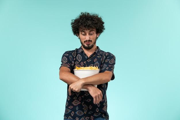 Junger mann der vorderansicht, der kartoffelspitzen auf dem filmkino des blauen kinos des männlichen kinos hält