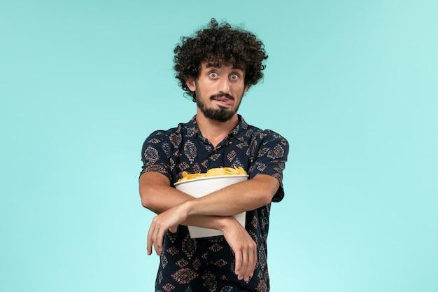 Junger mann der vorderansicht, der kartoffelspitzen auf dem hellblauen wandkino-kino des männlichen kinos hält