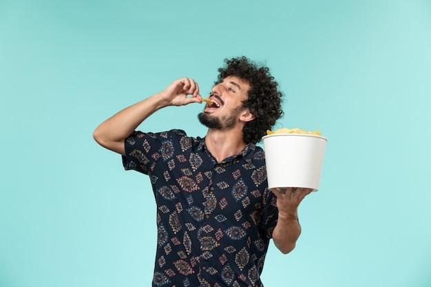 Junger mann der vorderansicht, der korb mit kartoffelspitzen hält und auf der blauen wand kino filme filmtheater mann isst