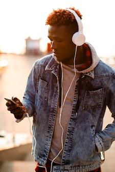 Junger mann der vorderansicht, der musikplaylist überprüft