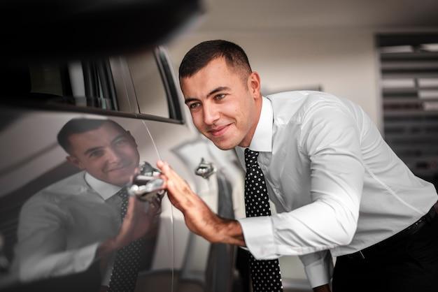 Junger mann der vorderansicht, der neues auto berührt