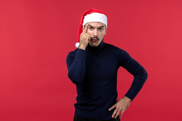 Junger mann der vorderansicht, der neujahrskappe auf dem roten hintergrund trägt
