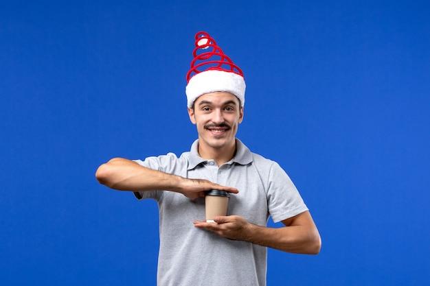 Junger mann der vorderansicht, der plastikkaffeetasse auf dem männlichen feiertag der blauen wand des neuen jahres hält