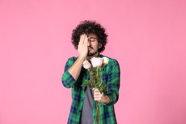 Junger mann der vorderansicht, der rosa rosen auf rosa farbe hält