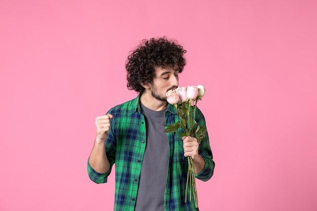Junger mann der vorderansicht, der rosa rosen auf rosa farben hält