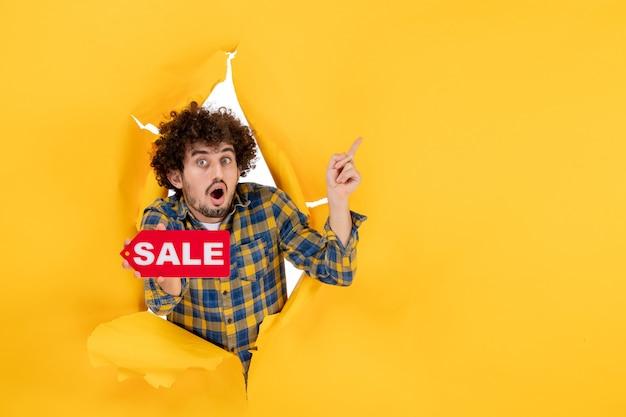 Junger mann der vorderansicht, der rote verkaufsschrift auf gelbem zerrissenem hintergrund hält