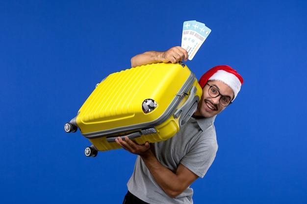 Junger mann der vorderansicht, der schwere tasche mit tickets auf urlaubsflugzeug der blauen wandflüge trägt