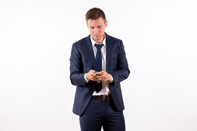 Junger mann der vorderansicht, der seine uhren im klassischen anzug auf menschlichem kostümmodemodell des weißen hintergrundgefühls hält
