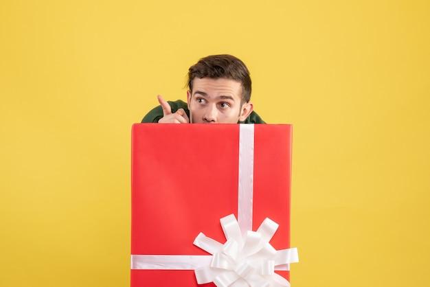 Junger mann der vorderansicht, der sich hinter der großen geschenkbox versteckt und etwas auf gelb betrachtet