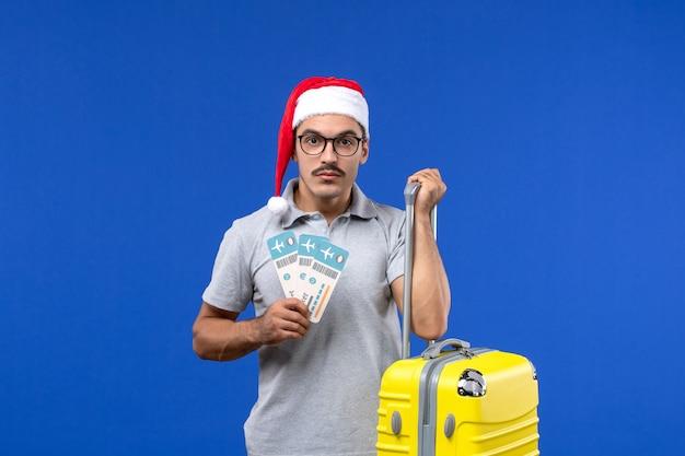 Junger mann der vorderansicht, der tickets und schwere tasche auf dem urlaubsflugzeug des blauen hintergrundflugs hält